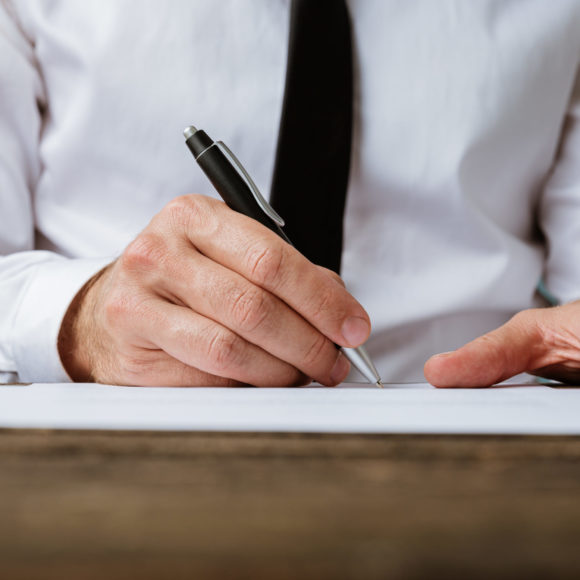 Low angle view of businessman signing a contract on rustic wooden desk.