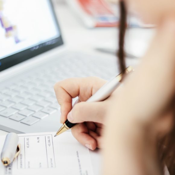 woman-with-a-pen-checking-financial-documents-taxe-5FG7KL4